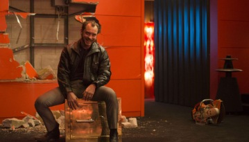 The only way Dom Hemingway knows how to make an entrance: Through the damn wall.