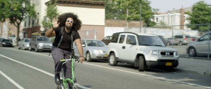 Of course Reggie Watts is driving around on a bike.